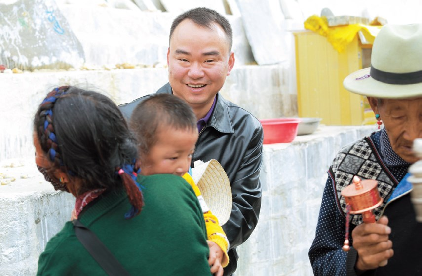 Lu Zhenchang, leader of the Sakya aid team, shares a smile with local Tibetans. — Tang Jie