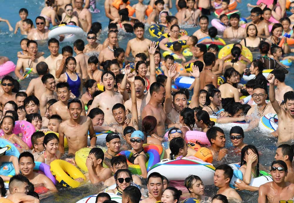 Crowds soak in a swimming pool in the southwestern city of Chongqing, yesterday, where the temperature surged to more than 37 degrees Celsius. The city issued an orange temperature alert — the second-most severe in the three-tier alert system. Even hotter days are coming. — Xinhua