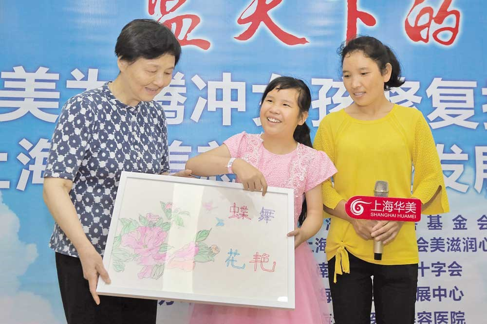 Gu Binbin presents her painting to Jin Minzhu, representing the Shanghai Charity Foundation, on Friday as her mother looks on. — Wang Rongjiang