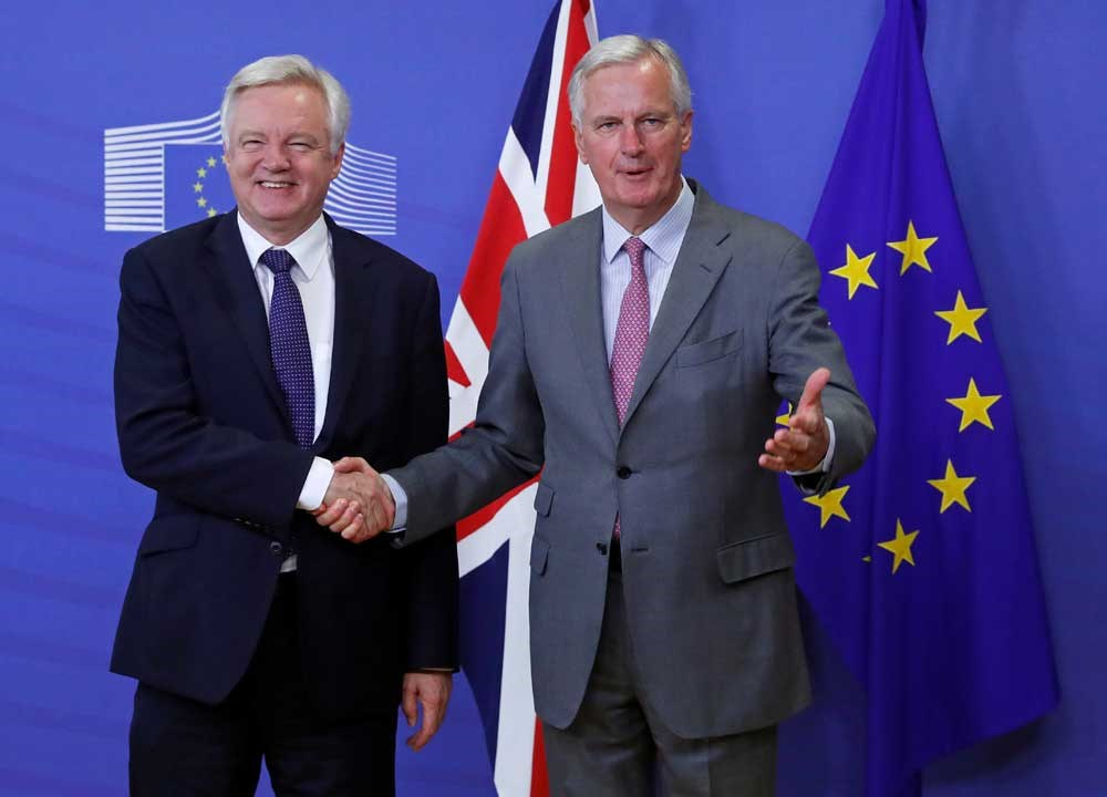 UK Secretary of State for Exiting the European Union David Davis (left) is welcomed to Brussels, Belgium, by Michel Barnier, the European Commission's chief Brexit negotiator, before the start of talks on divorce terms from the EU. Davis stayed only a few hours. — Reuters