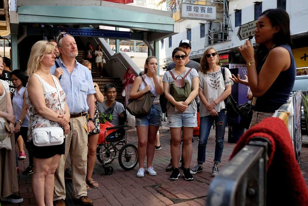 Tour guide Alla Lau (right) speaks to tourists during a visit to Mong Kok in Hong Kong. — Reuters