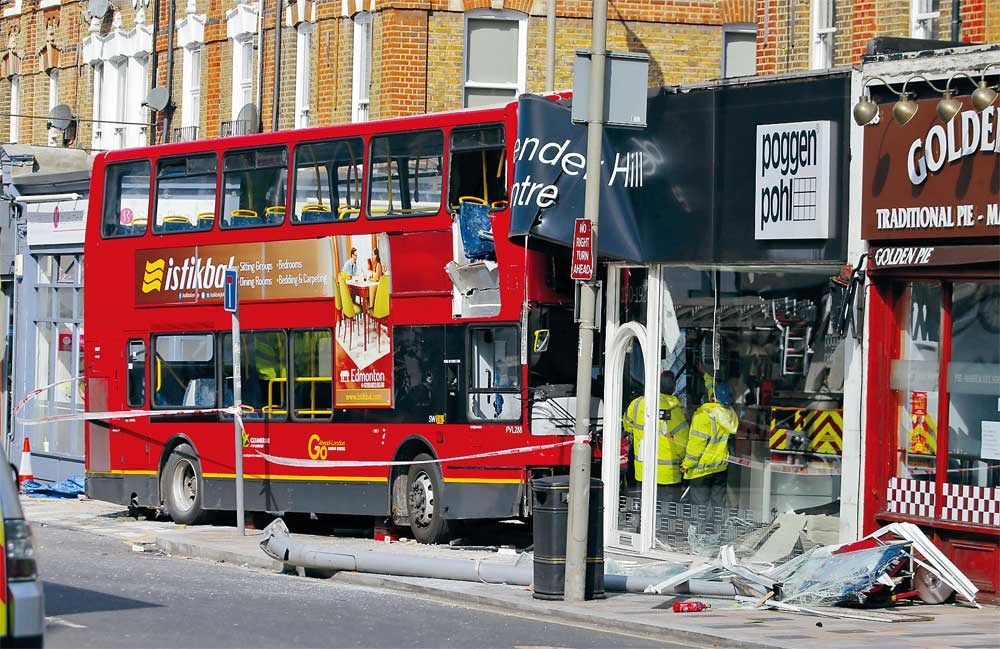 "Officials examine the scene of an accident where a bus ploughed into a shop on a busy street in southwest London yesterday, leaving 10 people injured. Two others were rescued when they were trapped inside by the debris. There was blood inside the bus, witnesses said. Passenger Amy Mullineux, a nurse, said the driver told her that he lost consciousness. ""He said he blacked out before the bus hit the shop,"" the 40-year-old said. ""He doesn't remember hitting anything."" Another passenger, Andrew Matthews, 34, said around a dozen people were on the bus when it began to drift off the road. ""As soon as the bus came to a stop there was yelling, screaming,"" he said. The accident happened on Lavender Hill, best known for the 1951 movie ""The Lavender Hill Mob."" — AFP"