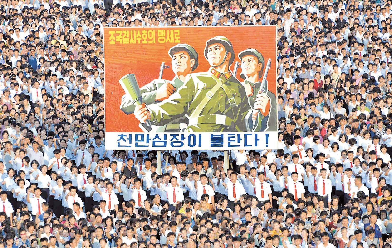 North Koreans rally to support the country's stance against the US in Pyongyang on Wednesday. North Korea elaborated on a threat to attack the US Pacific territory of Guam. — AFP