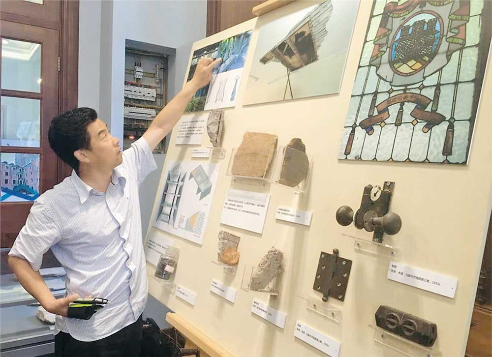 "Jiang Jiang, deputy director with the Xuhui housing management bureau, points to examples of ""lost skills"" that have been collected and cataloged at an exhibition in Xujiahui. — Bob Yang"