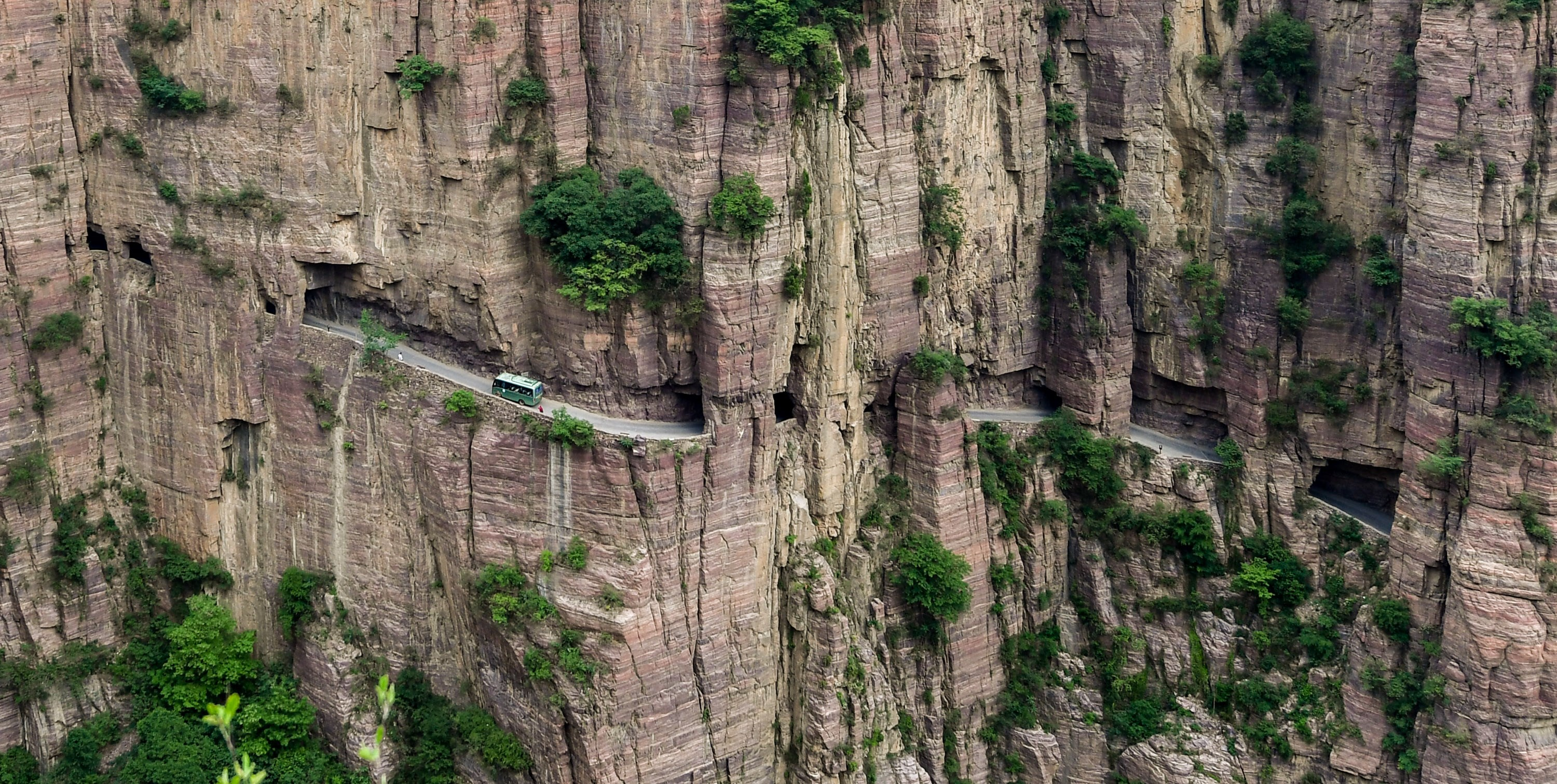 A sightseeing bus travels through the tunnel that connects Guoliang Village in Henan Province to the outside world.