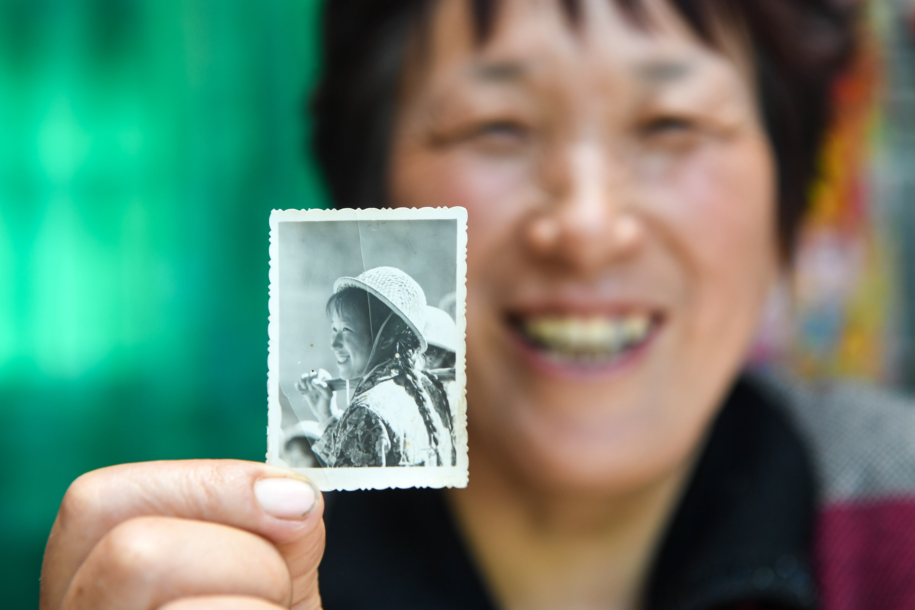 Guoliang Village resident Shen Xiangrui shows a picture of her in 1975.