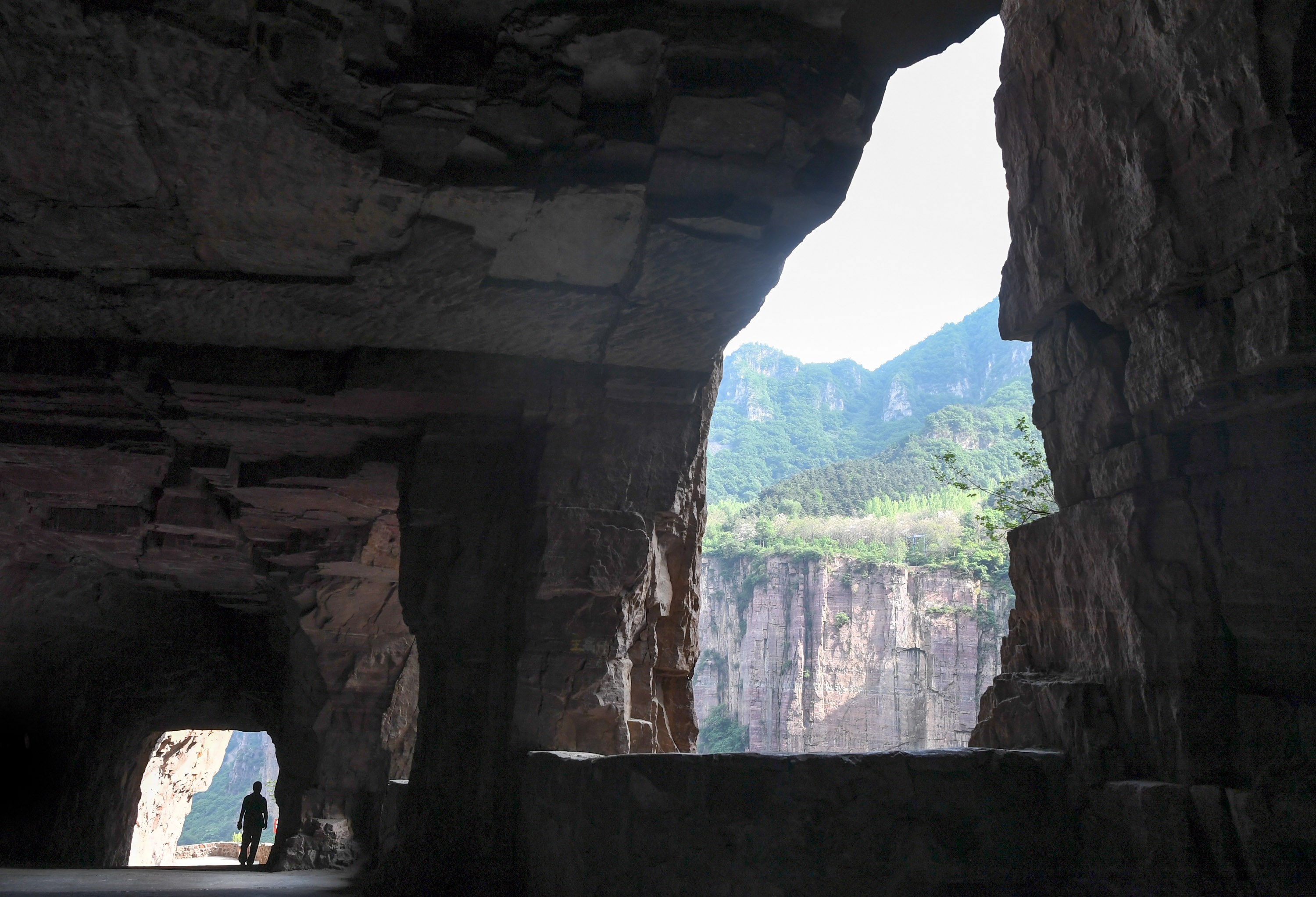 A tourist admires the cliff tunnel that was made purely by hand by Guoliang Village residents.