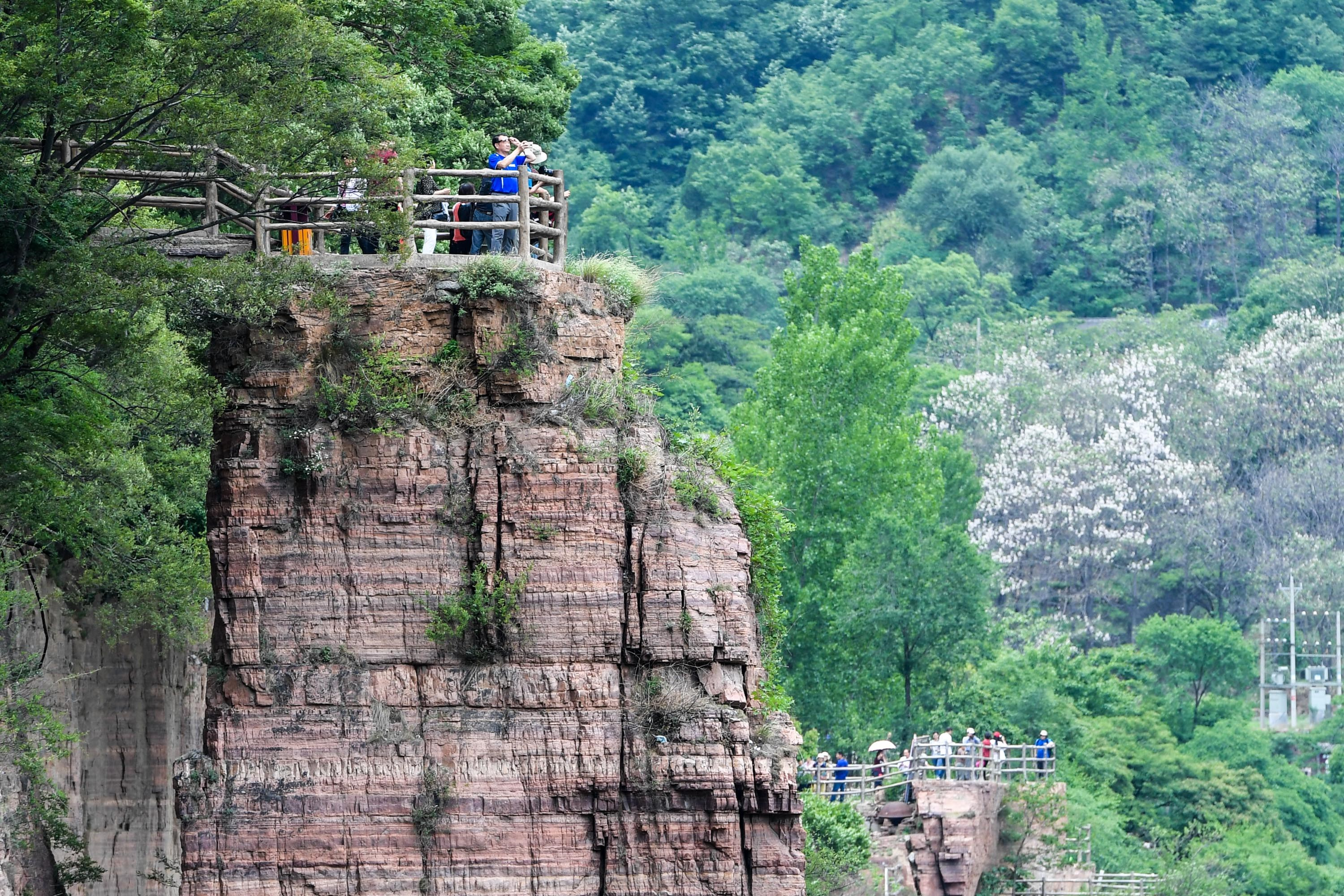 Tourists enjoy a grand view of Hongyan Canyon from a sightseeing stand in Guoliang Village.