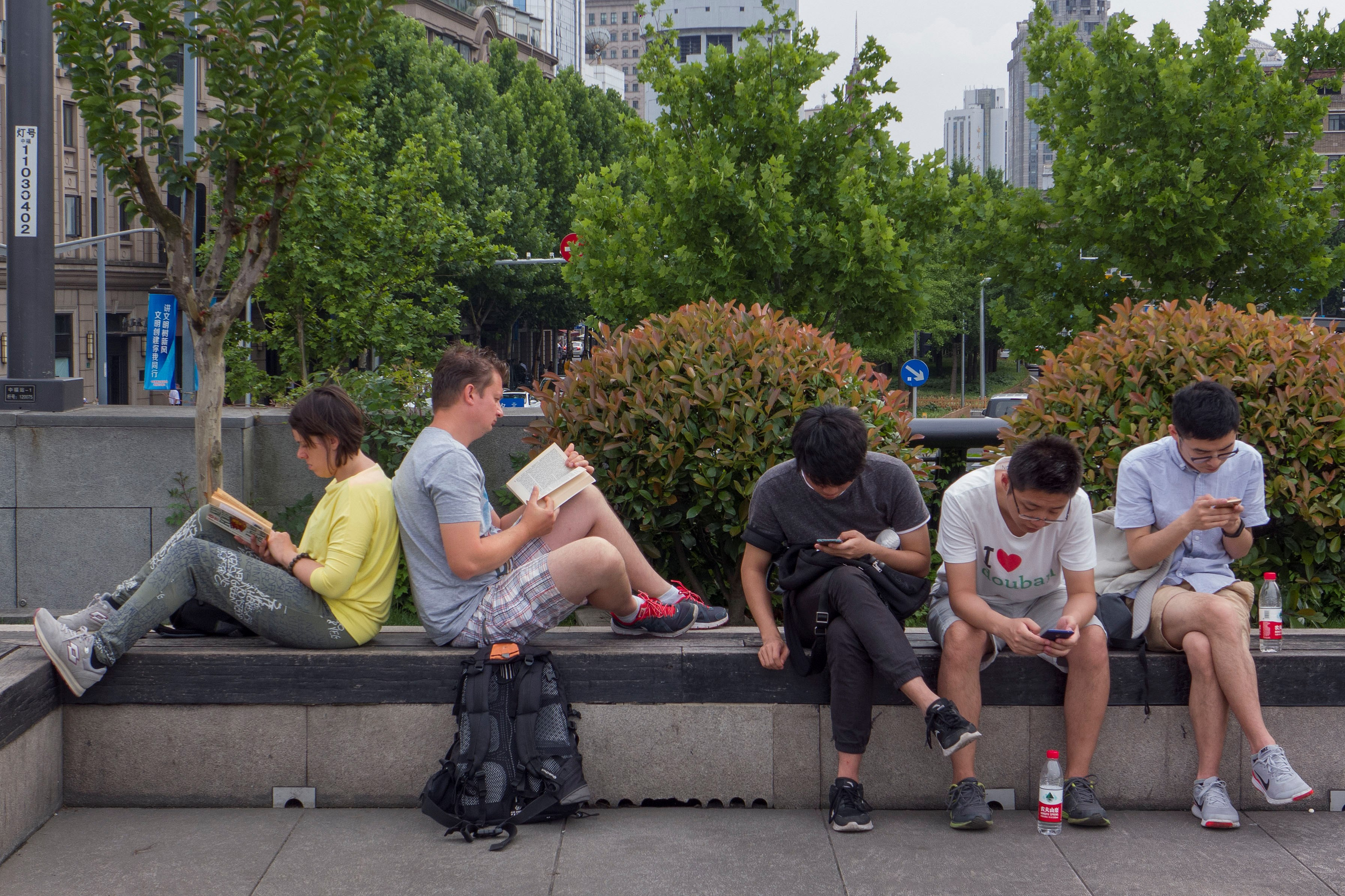 An expat couple read books as three young men browse their mobile phones at a public space in downtown Shanghai. — Wang Rongjiang