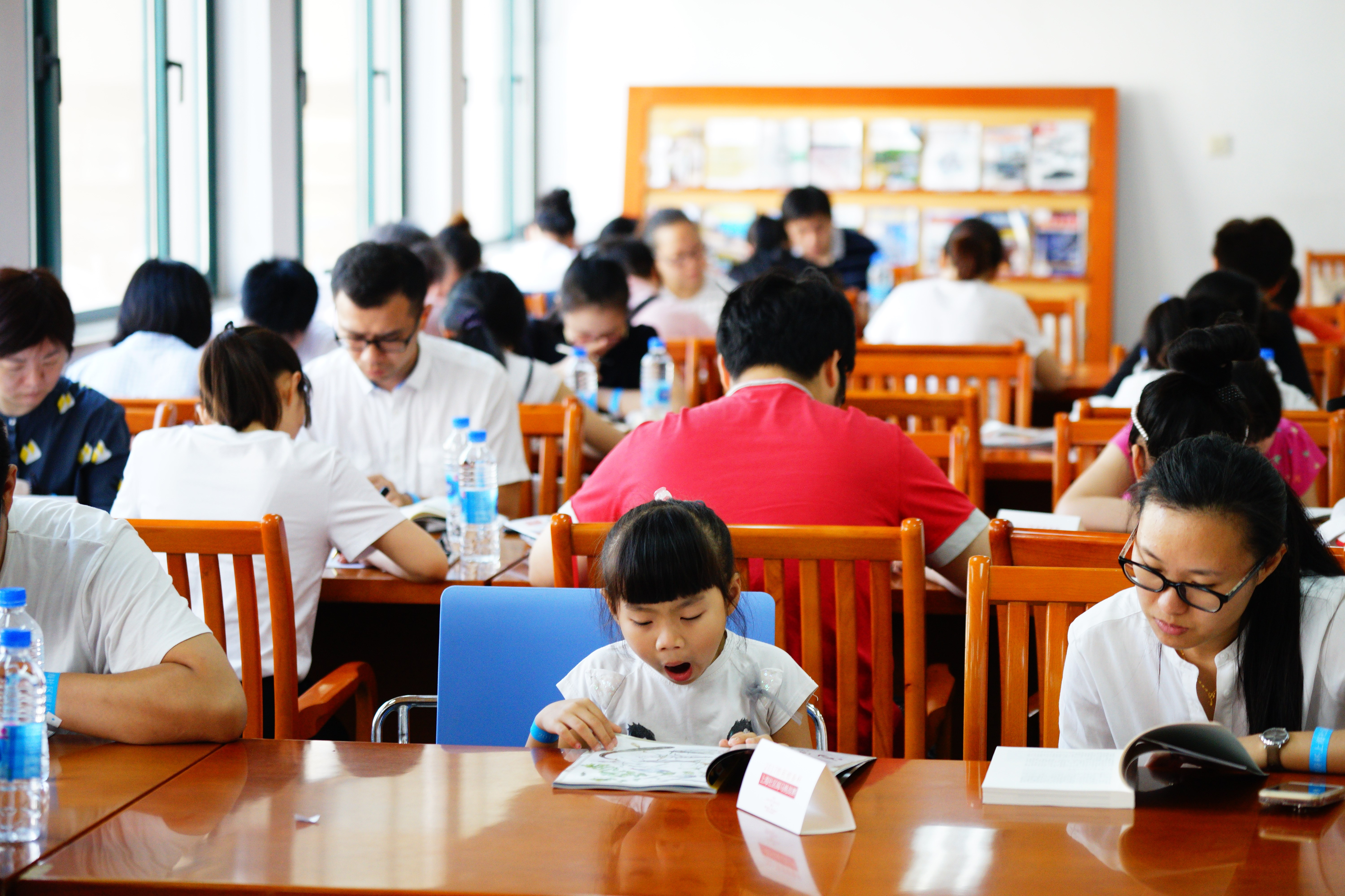 A girl yawns as she participates in a reading marathon at Jing'an District Library on August 4. — Jiang Xiaowei