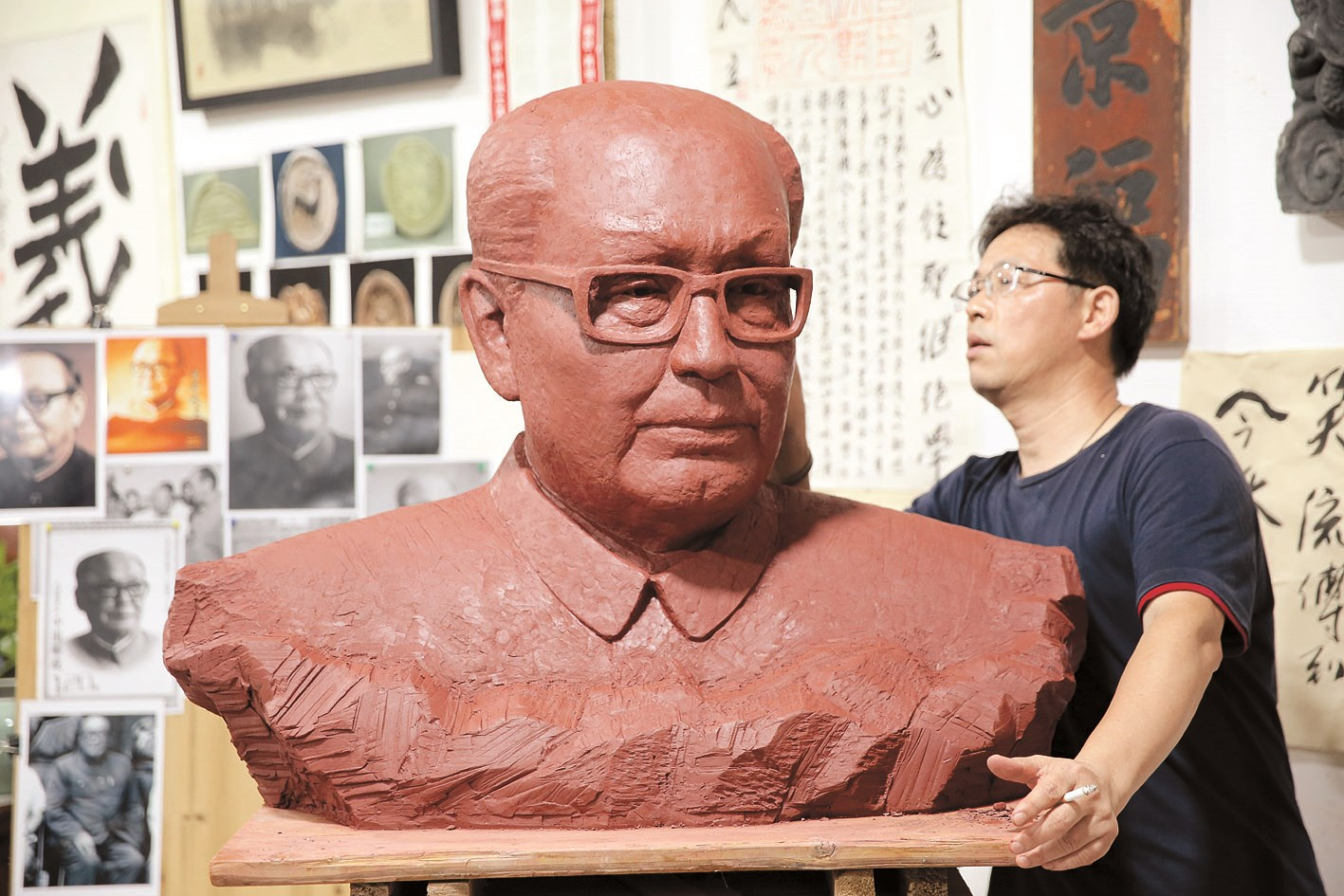 Yin Xiangming, a folk artist from Jiangsu Province, makes a purple clay statue of Ulanhu, secretary of Communist Party of China Inner Mongolia Committee, at the Ulanhu Memorial Hall. Ulanhu from 1959 helped bring thousands of orphans to the region where there was enough milk and meat to feed them. — Imaginechina
