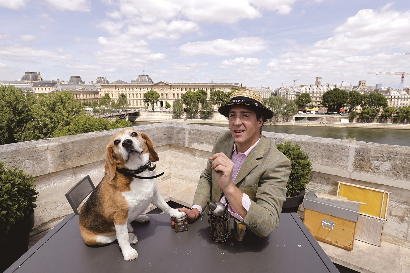 Audric de Campeau posing with his dog as he checks beehives set on the roof of the Monnaie de Paris in Paris. — AFP