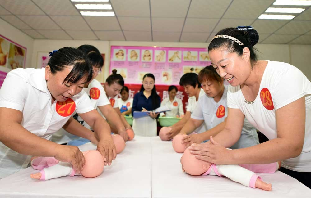 Domestic helpers demonstrate their skill in caring for babies, though not real ones in this case, during the final of a competition in Fengshui, north China's Hebei Province, yesterday. — Xinhua