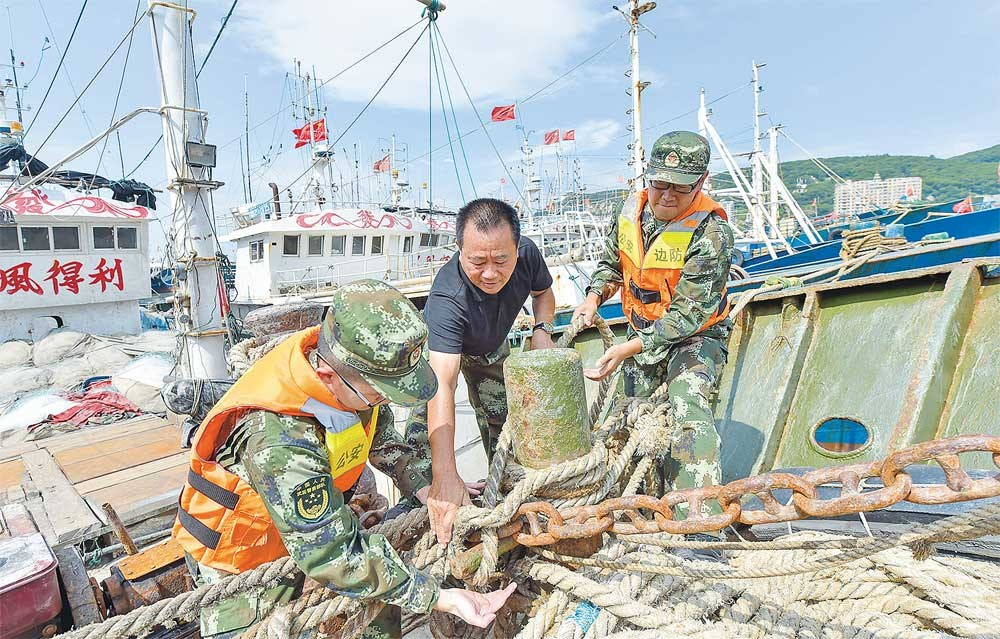 Armed police officers help a fisherman tie up his boat at a port in Fuzhou in southeast China's Fujian Province yesterday as residents prepared for the arrival of Typhoon Talim. More than 200,000 people in Fujian and Zhejiang provinces have been evacuated. Talim is expected to make landfall tonight along Zhejiang's northern coast as a strong typhoon, packing gusts of up to 48 meters per second. It could also strengthen into a super typhoon with winds of 52 meters per second. Shanghai will escape the worst, however, as the storm has changed direction. Taiwan issued a warning to ships and airlines canceled some flights yesterday as the island braced for the typhoon's arrival. It was expected to hit cities in the north, including Taipei, before hurtling toward China's mainland, potentially as a super typhoon. Talim was expected to gain in strength as it sweeps toward the island's northern cities. — Xinhua