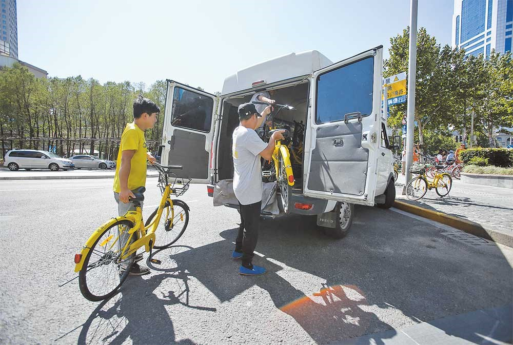 Workers remove shared bikes from the pavement at Yan'an Road East, Huangpu. — Jiang Xiaowei