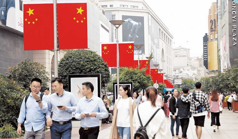 The flags are flying and a festive atmosphere pervades on Nanjing Road E — reputed to be China's premier shopping street — with the National Day holiday just around the corner. — Imaginechina