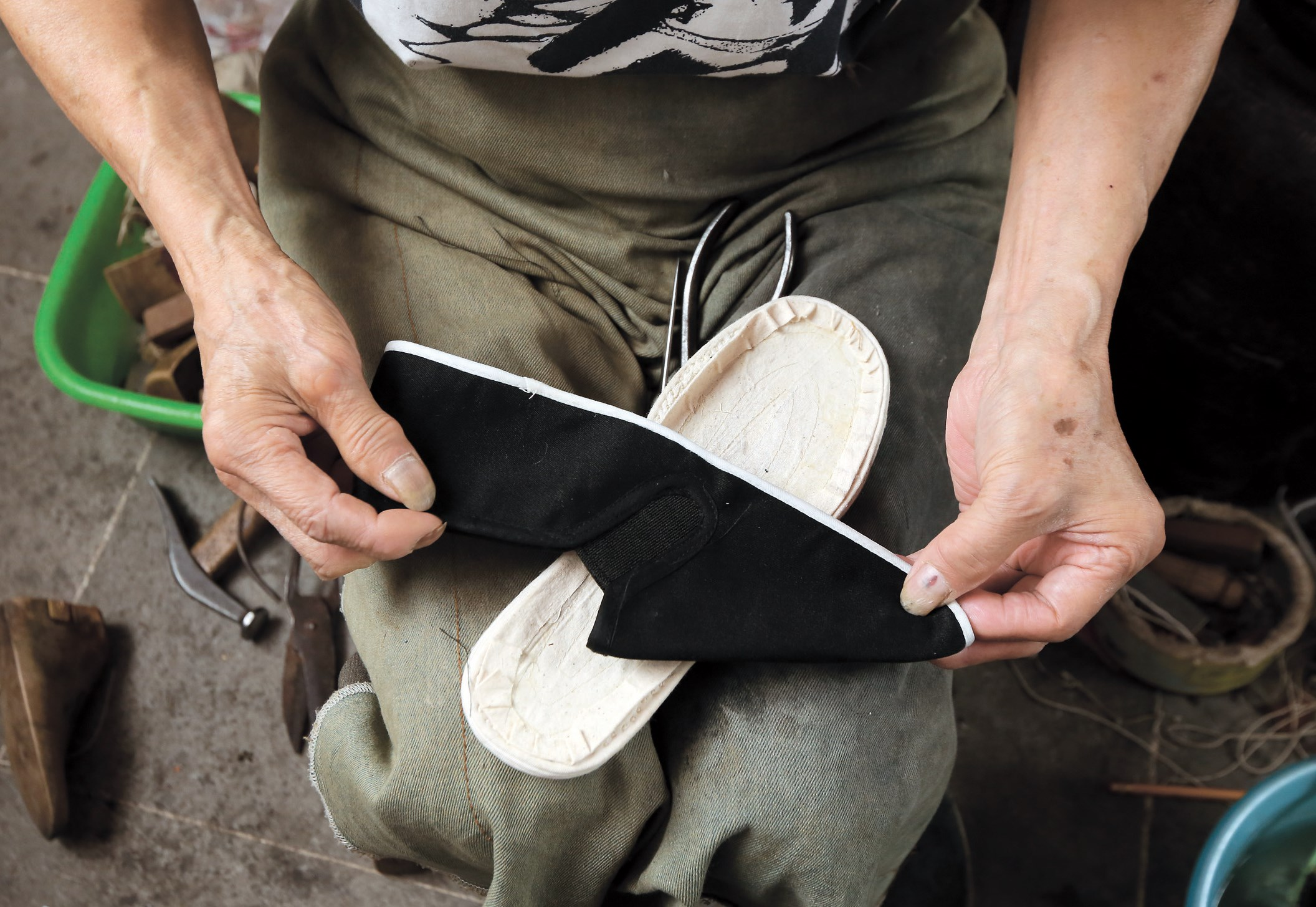 Strong, scarred and knobby, the hands of Yang Shenxi, 80, have weathered decades of work as a shoemaker. — Wang Rongjiang