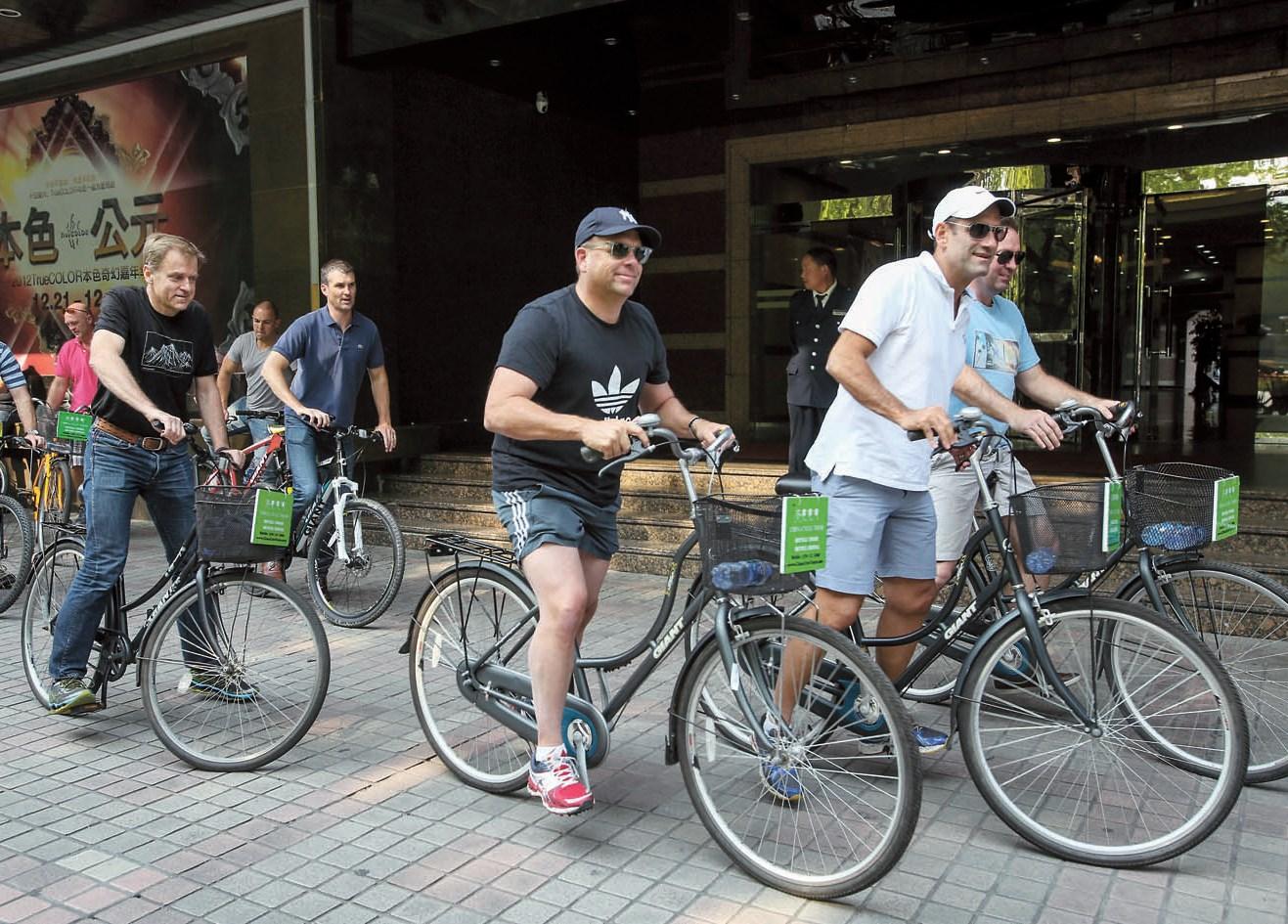 A group of expats ride bikes in downtown Shanghai. — Wang Rongjiang