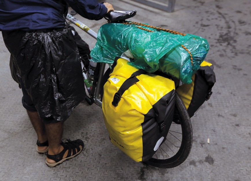 The bike is Dnyaneshwar Yeotkar's home, which is stuffed with necessities for the road. — Wang Rongjiang