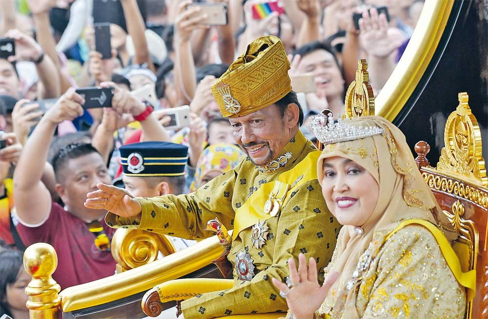 Brunei's Sultan Hassanal Bolkiah and Queen Saleha ride in a royal chariot during a procession to mark his golden jubilee of accession to the throne in Bandar Seri Begawan as the all-powerful sultan celebrated the 50 years on the throne yesterday with lavish events, including a glittering procession, a 21-gun salute and a ceremony at his vast, golden-domed palace. — AFP
