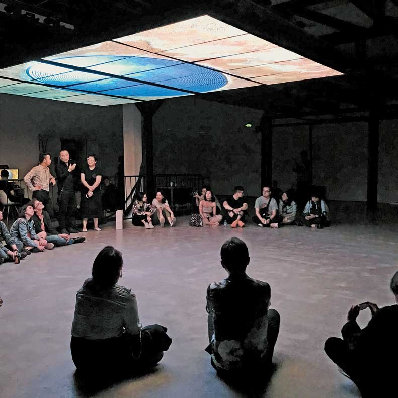 "Visitors enjoy Zhang Ding's video ""Vortex""on display at ShanghART Gallery."