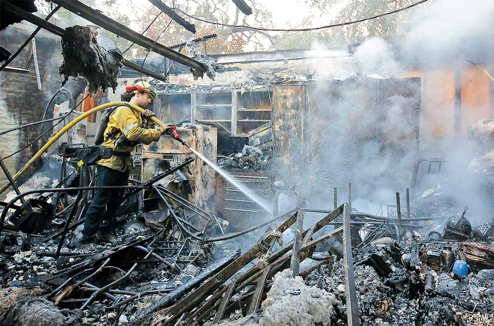 Firefighter Nick Gonzalez-Pomo, of the San Rafael Fire Department, hoses down smoldering ashes in a garage in Napa, California, on Tuesday. Firefighters battling wildfires in California's wine country faced the prospect of new outbreaks as dry, windy conditions are due to return to an area where blazes have killed at least 17 people and destroyed 2,000 homes and businesses. Gusts of up to 80 kilometers per hour and 10 percent humidity were forecast for today in the region, where 17 fires have forced 20,000 people to flee their homes in one of the deadliest wildfire outbreaks in Californian history, officials said. New evacuation orders were posted across Sonoma County, north of San Francisco. Some 155 people were missing in Sonoma County, although 45 others had been found and some of those unaccounted for may be due to confusion surrounding evacuations. California Governor Jerry Brown has declared a state of emergency in several northern counties, as well as in Orange County in southern California. — Xinhua