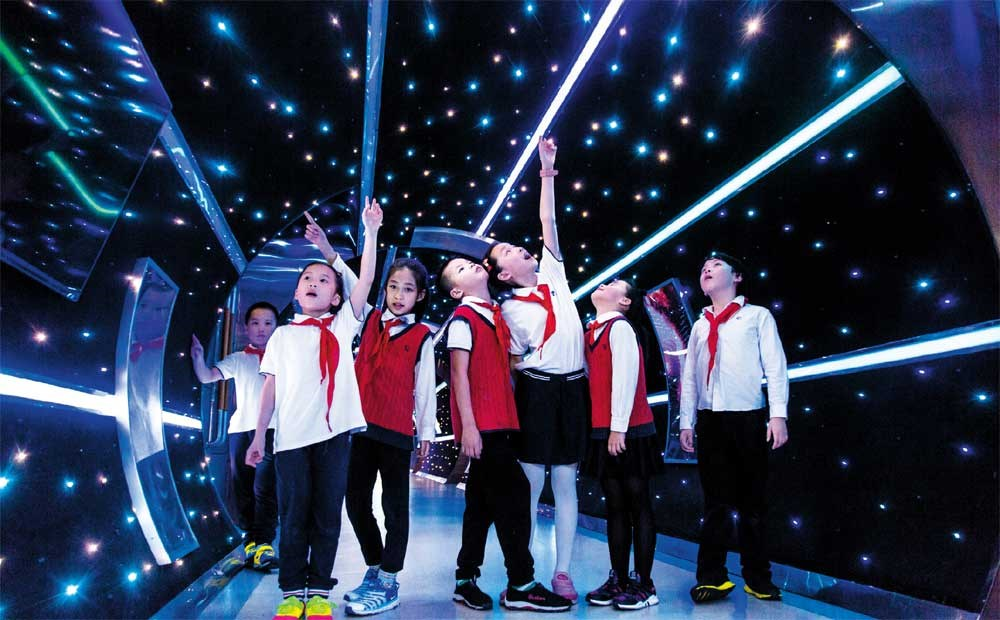 """A group of excited students walk through a """"space tunnel"""" at Changjiang Experimental Primary School in Hangzhou. The school has changed a dimly-lit corridor in the school building by installing more than 1,000 LED lights. In addition, short films about natural science are also played in the tunnel to tell some basic knowledge. — Imaginechina"""