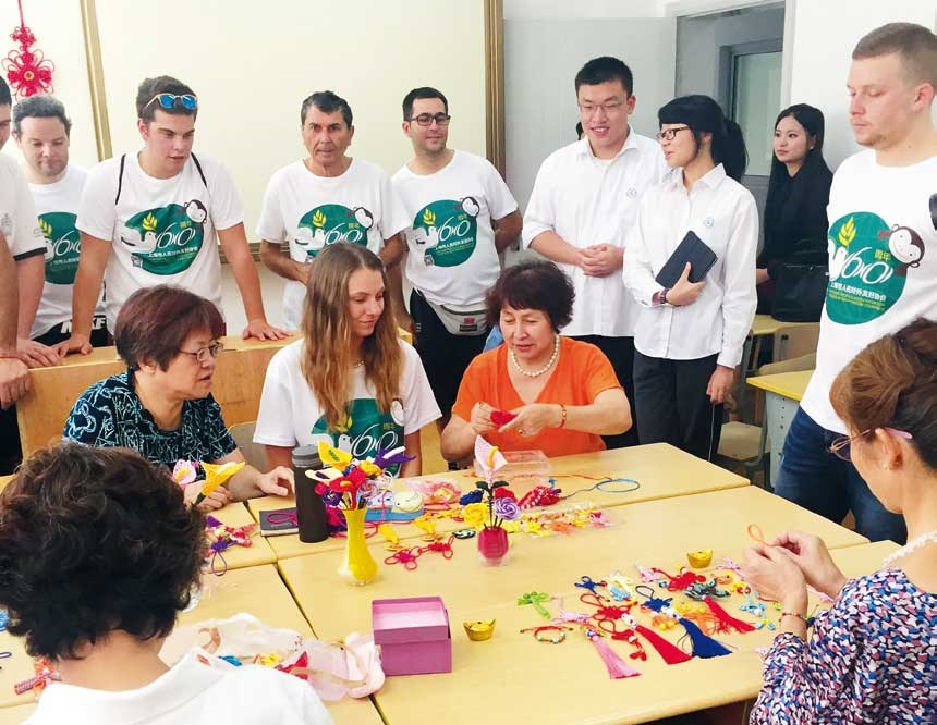 Foreign tourists learn to make paper artwork from local masters in Caoyang community.