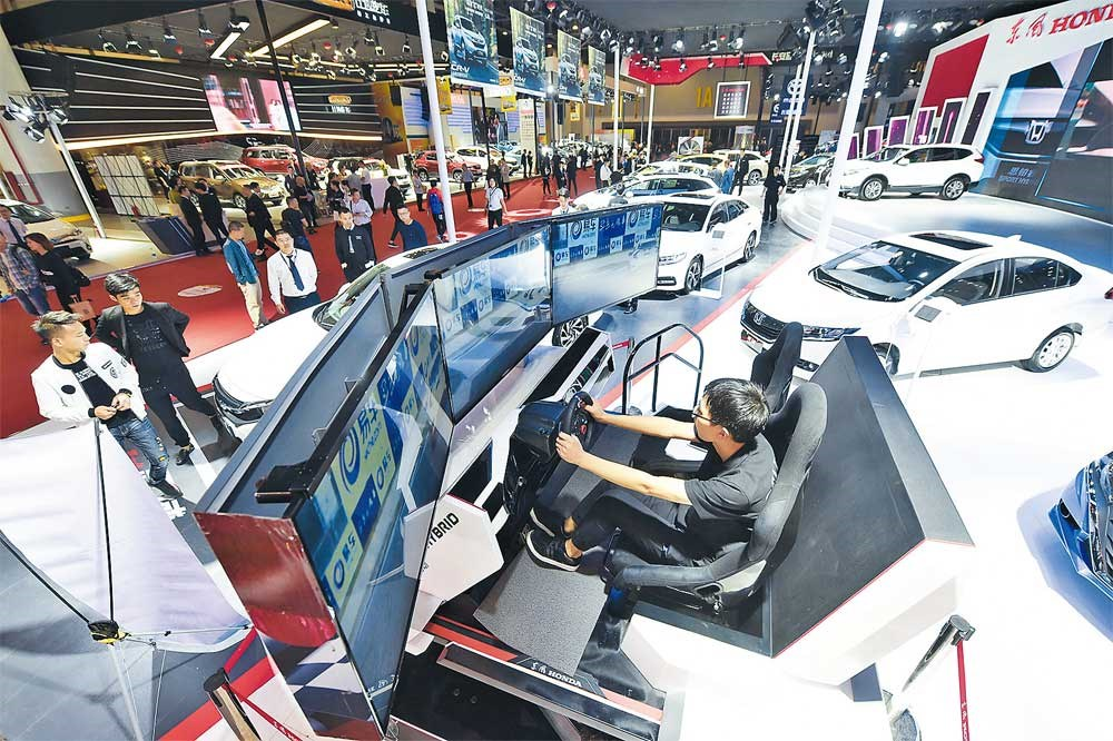A visitor to the Hangzhou International Auto Expo tries a simulator yesterday. The five day auto show attracted over 100 automakers from around the world. — Xinhua