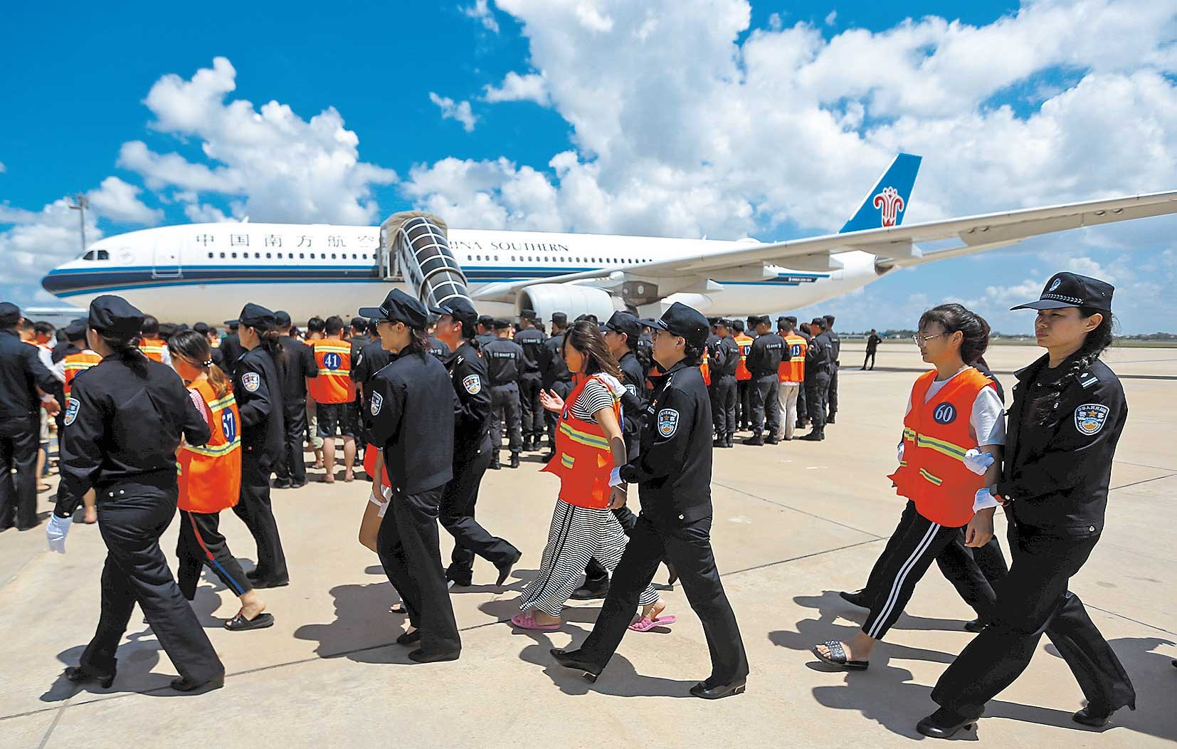 Chinese nationals (in orange vests), who were arrested over a suspected Internet scam, are escorted by Chinese police officers before they were deported at Phnom Penh International Airport, in the Cambodian capital, yesterday. A total of 74 Chinese nationals arrested for telecom fraud were sent back to China from Cambodia yesterday. The suspects were accused of being involved in more than 60 major transnational telecom frauds involving over 7 million yuan (US$1.1 million). They were captured in Phnom Penh, Pailin and Sihanoukville. A large collection of bank cards, computers and mobile phones were also seized during the raids. — Reuters